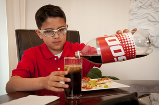 Kid pouring a large glass of soda - Play Every Day message reveals health harms of sugary drinks.