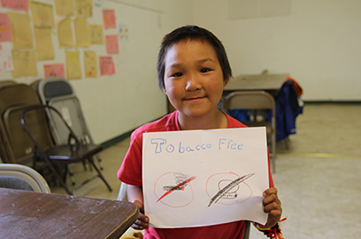 "young boy from Yukon- Kuskokwim proudly displays his hand drawn ""no tobacco, no Iqmik"" poster."