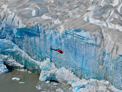 Helicopter flying by glacier