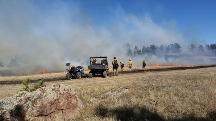 View of burn zone with firefighters watching