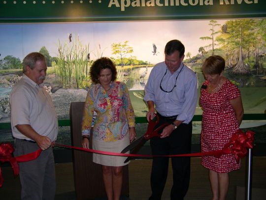 Secretary Vinyard ceremoniously cuts a ribbon at the Apalachicola National Estuarine Reseach Reserve.