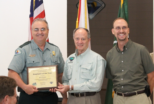 Florida Park Service Director Donald Forgione presents Bill Allman with the Employee of the Year Award with District Three Chief Larry Fooks.