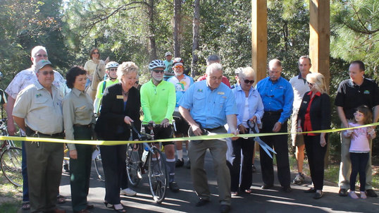 Event participants cut the ribbon to reopen the Tallahassee-St. Marks Trail.