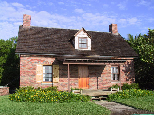 Front of the two-story, brick, Lighthouse Keeper's Quarters showing the porch, surrounded by grass and yellow flowers.
