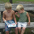 Two boys read a book at Alfred B. Maclay Gardens State Park