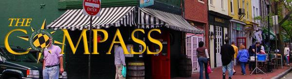 Compass logo over photo of main street retail