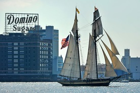 Image of Domino factory with Pride of Baltimore sailing past during Sailabration 2014