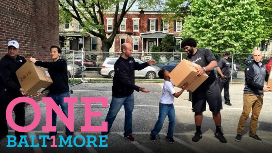 "IMAGE: Baltimore City residents pass boxes of relief supplies down the line. The words ""One Baltimore"" are displayed on the image."