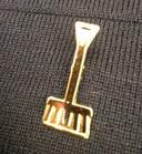 golden shovel lapel pin