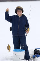 Young boy ice fishing during Michigan's winter
