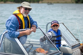 An older man and young girl wearing safety gear on a boat.