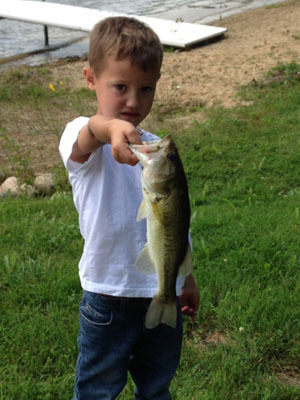 Young boy holding largemouth bass