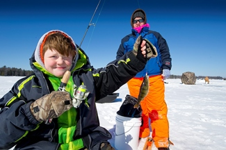 young boy ice fishing holds up his yellow perch