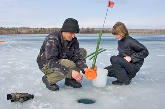 Man and child setting up a tip-up while ice fishing