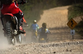 Low angle shot from behind of people riding dirtbikes