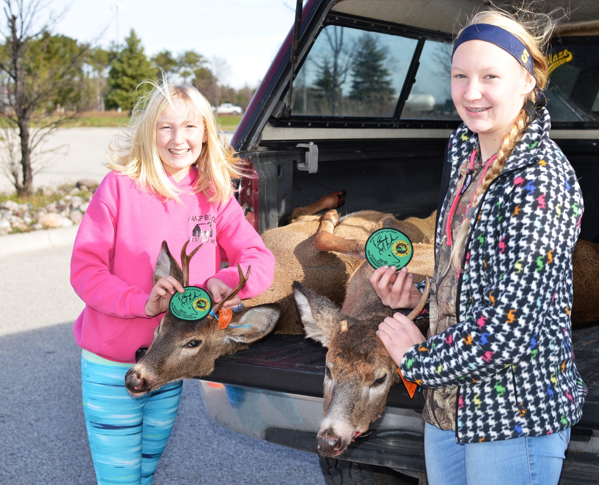 Two girls from Indian River display their bucks