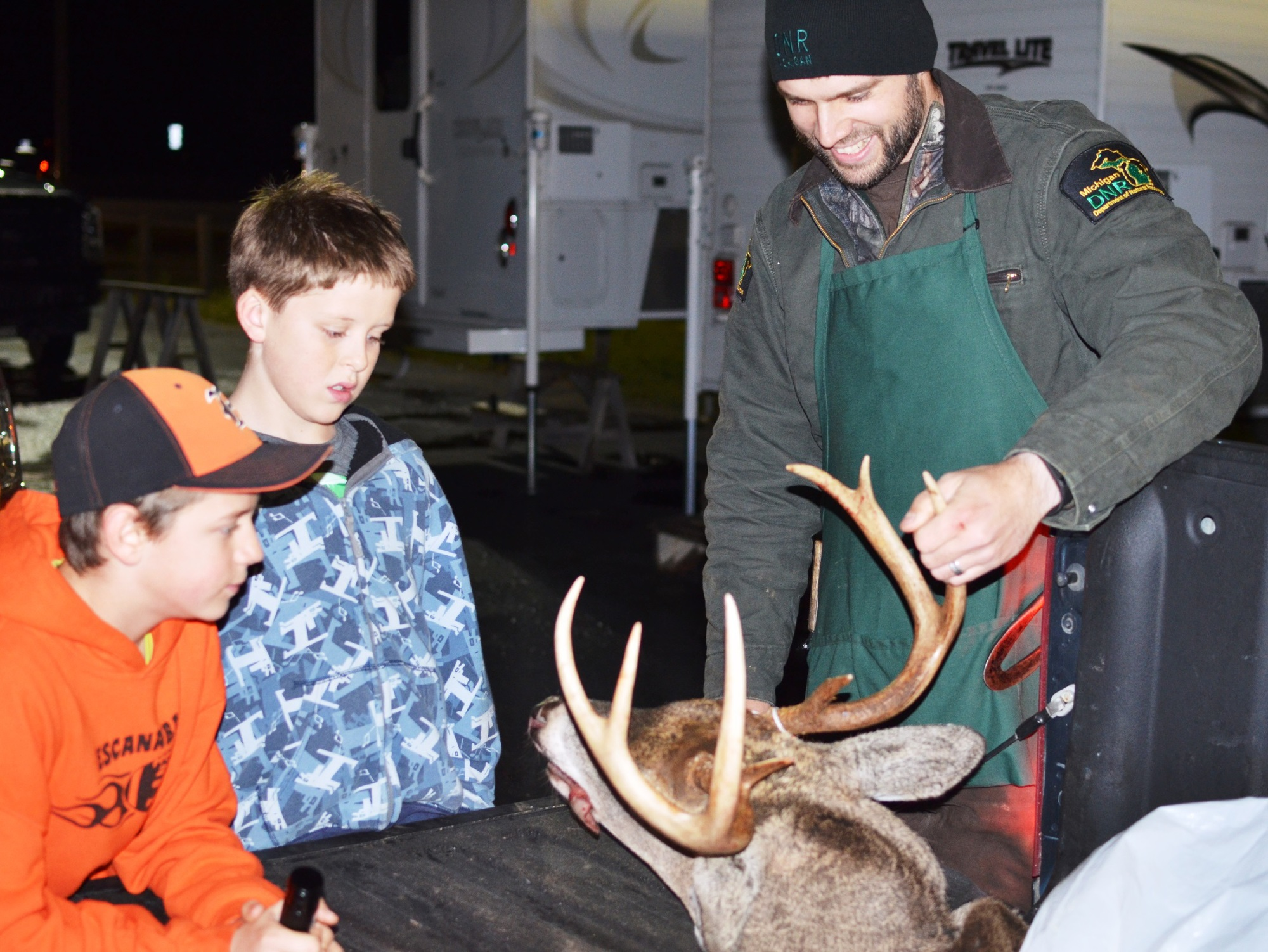 Two kids watch a DNR wildlife biologist check in a buck