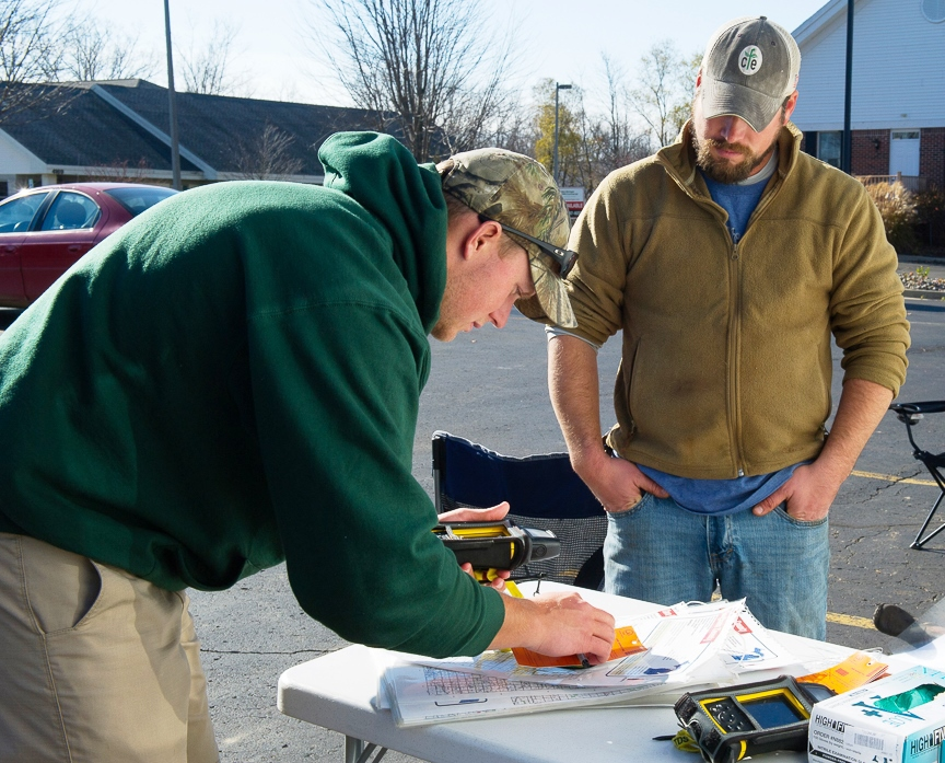 A Michigan Department of Natural Resources staff worker stands near a folding table, assisting a hunter who is bringing a deer in for testing.