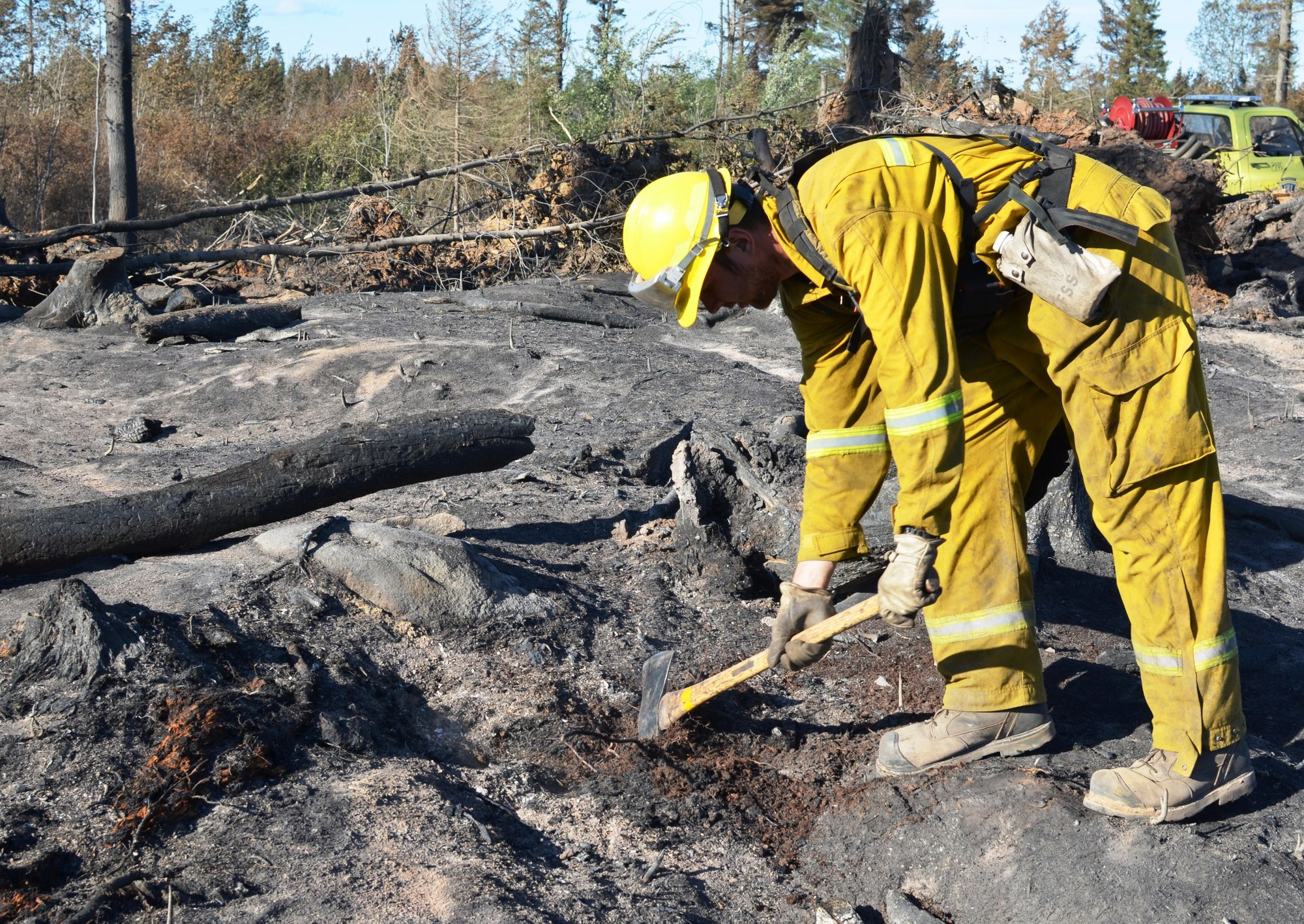 A fireman works on putting out a hot spot on the Marquette County Road 601 fire. The fireman was among several sent to Manitoba this past summer.
