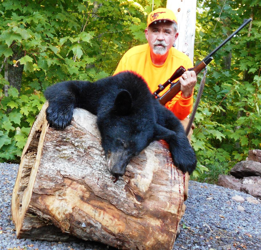 Hunter Phil Barry of Hancock is pictured with his gun and a black bear he shot.