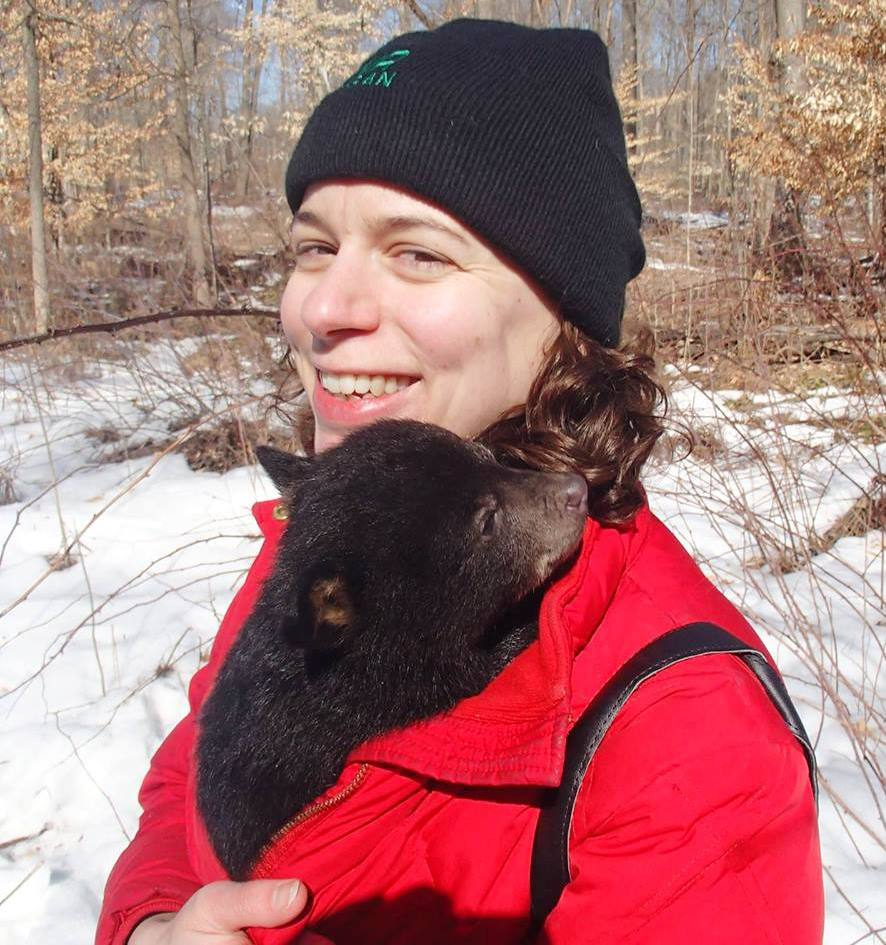 Sarah Mayhew, DNR wildlife research biologist, is in a red jacket with a bear cub tucked inside.