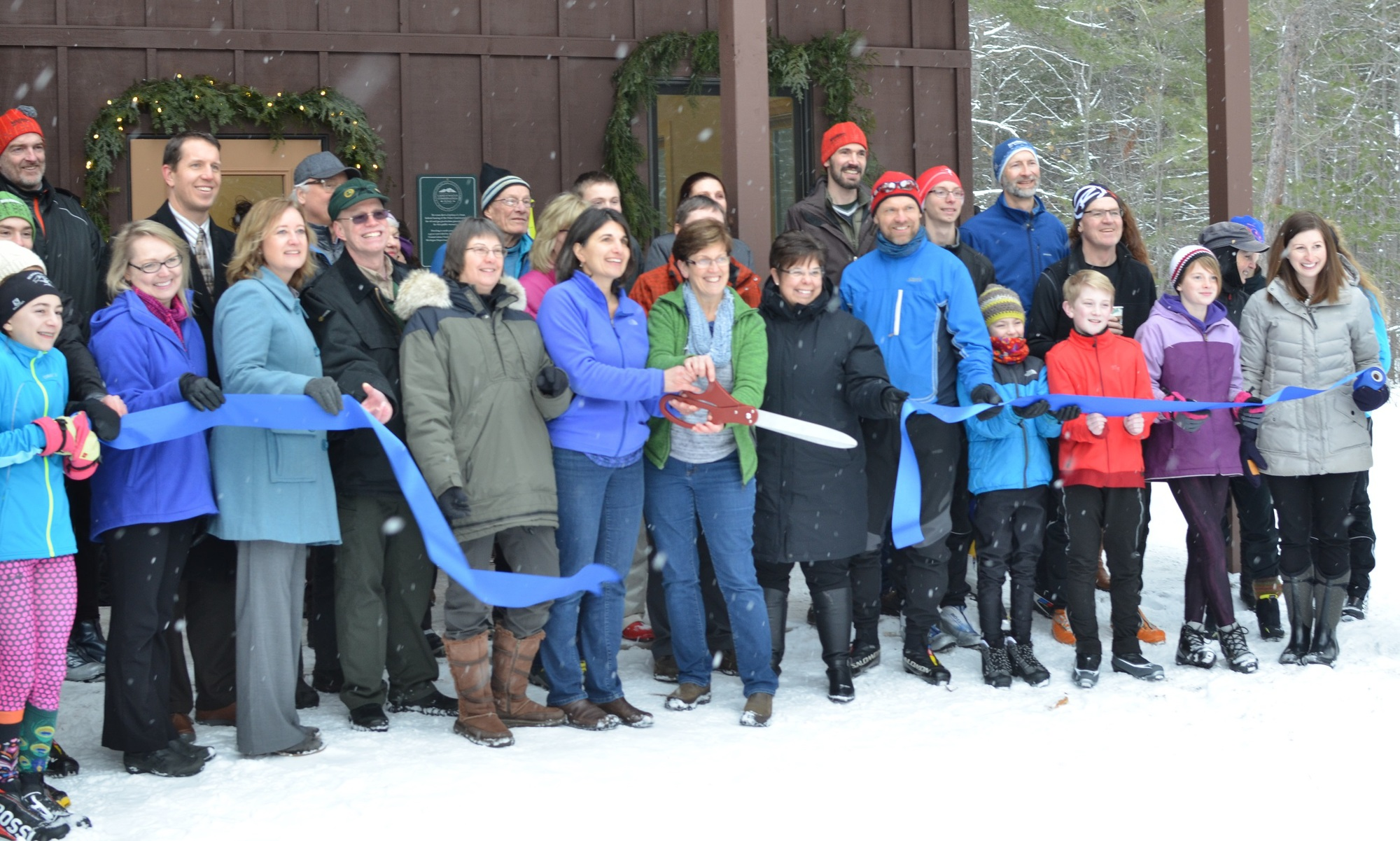 A large group of skiers, partners and others stands in front of the new warming hut for a ribbon-cutting ceremony at Blueberry Ridge.