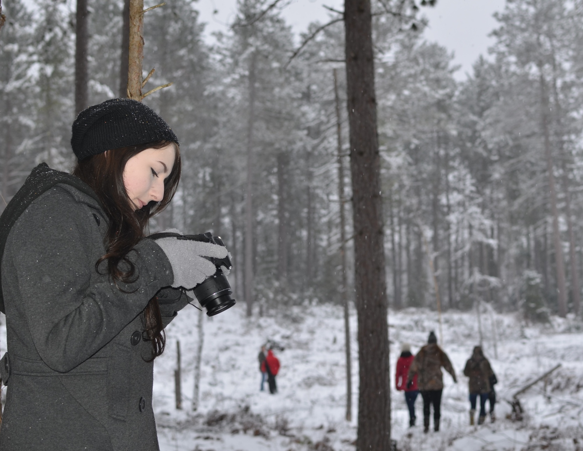Andrea Gerstner, 16, of Sagola looks at an image she just shot in a snowy forest.