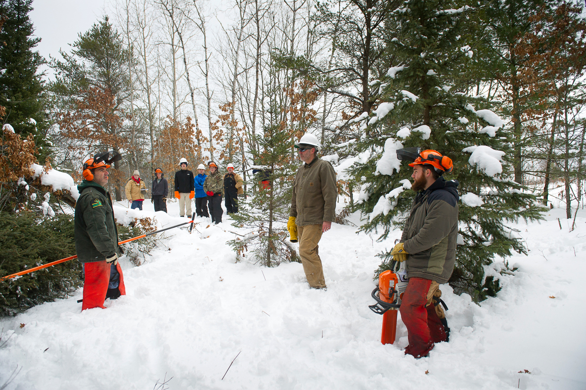 In a snow-covered open area, Michigan Department of Natural Resources wildlife biologist Brian Piccolo, left, talks with a group of volunteers.