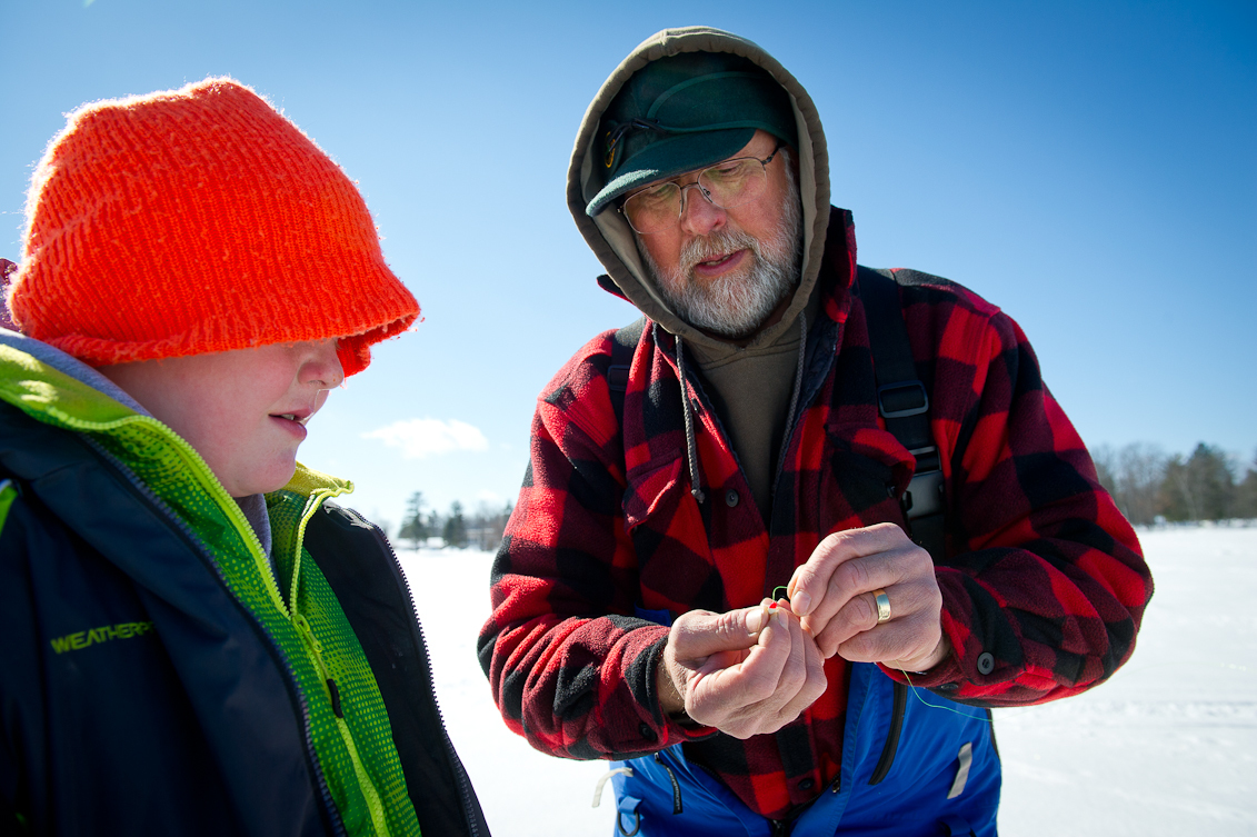 On an ice-covered lake, under a blue winter sky, state park interpreter John Zakrajsek helps an academy ice fishing seminar participant.