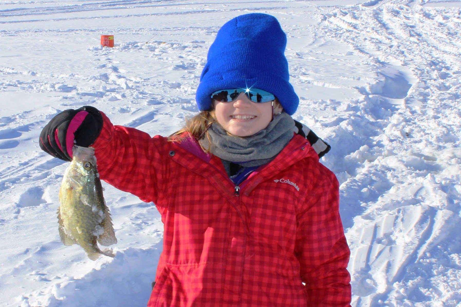In a red coat and blue hat, a young girl holds up a fish she caught from an ice-covered lake.