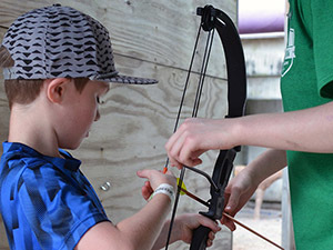volunteer helping boy shoot bow and arrow