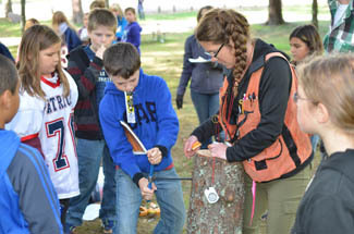 A student takes a crack at coring a tree at a Forestry Field Day in Marquette County.