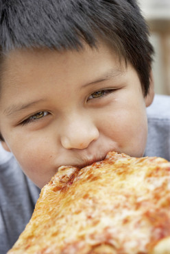 Boy eating cheese pizza