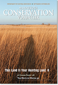 September–October 2013 Minnesota Conservation Volunteer magazine cover showing hunter's shadow across a dry grassland