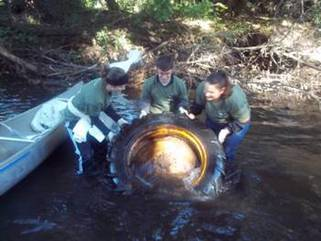 Volunteers lugging a giant tire out of the river