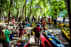 Boats and paddlers lined up along a wooded shore waiting to put in.