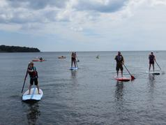 Stand up paddleboarderso f all ages and kayakers on Lake Superior