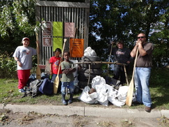 2 adults and 3 kids standing next to their piles of trash and tires collected through an Adopt-a-River cleanup with paddles in hand.