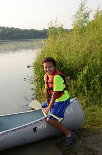 Young boy stabilizing a canoe at a 2013 I Can Paddle! On the Lake program at Fort Snelling State Park.