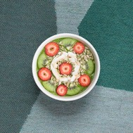 Photo of a bowl of cut pieces of kiwi, strawberries, and bananas with seeds, sitting on turquoise fabrice