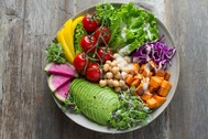 Photo of a colorful bowl of cut-up avocado, lettuce, cherry tomatoes, raw beets, etc.