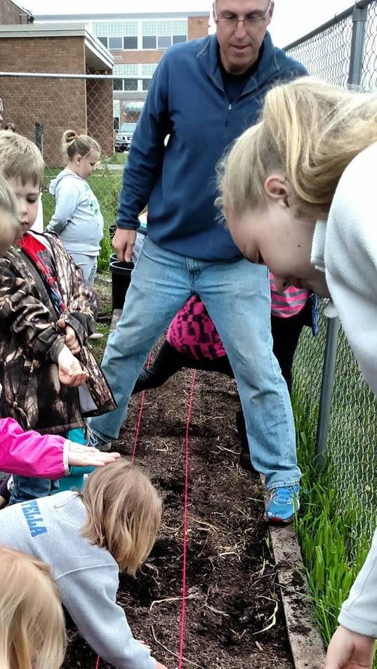 Tom Frericks works with students in their school garden