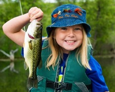 Girl holding up a fish and smiling