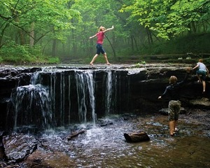 Girl walking across waterfall at Platte River State Park.