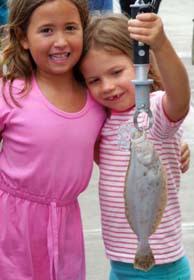 two happy kids with summer flounder
