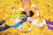 kids laying in fall leaves