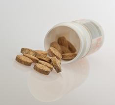 Open bottle of vitamins spills contents