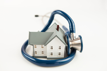 Illustration of a blue stethoscope wrapped around tiny house
