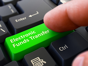 """finger presses green computer key marked """"Electronic Funds Transfer"""""""