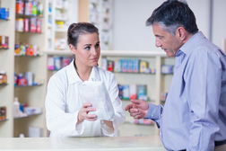 Pharmacist trainee gives a bag of prescriptions to a customer in a drugstore.